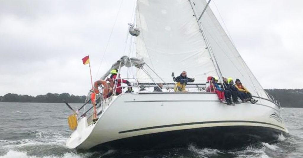 Segelyacht AHAB auf der Ostsee beim Segeln am Wind, mit Wind von Steuerbord, einer Regatta. Schräglage und Crew auf der Hohen Kante, Beine nach außen.