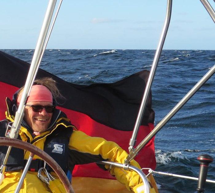 Skipper mit Ölzeug und Weste vor wehender Bundesflagge am Heck. Segeln raumschots im Herbst bei Sonne auf der Ostsee.