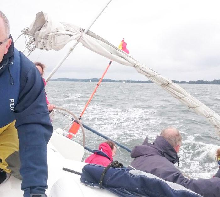Regattacrew am Wind auf der Zielkreuz. Schräglage, alle mit Rettungswesten. Segeltörn Ostsee, Nebensaison.