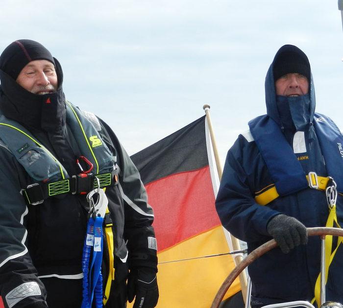 Ablösung für den Rudergänger. Ölzeug, Rettungsweste, Lifebelt. Segeltörn im Herbst auf der Ostsee.