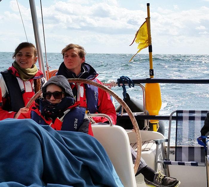 Entspannung im Cockpit im Herbst auf der Ostsee. Vier Gäste mit Rettungswesten beim Mitsegeln.