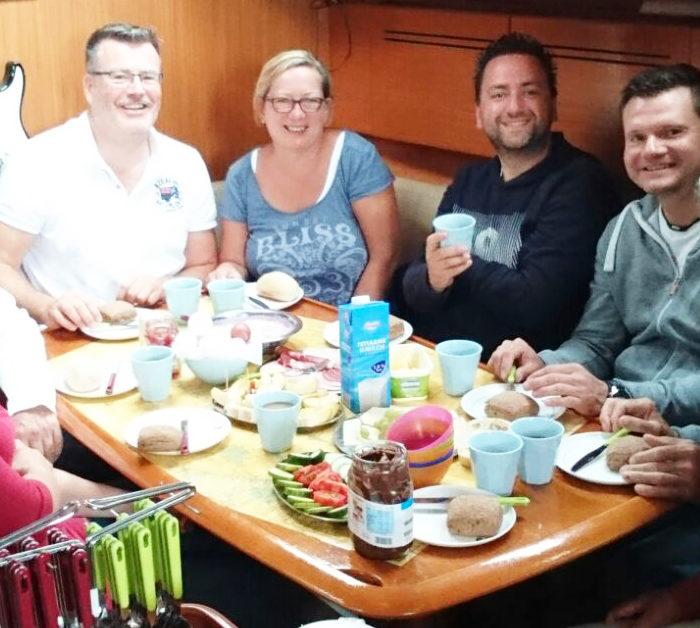 Frühstück unter Deck. Hier ist es auch beim Segeln im November warm. Acht Gäste haben bequem Platz am Salontisch.